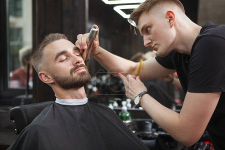 Handsome man looking relaxed while getting his beard trimmed by barber