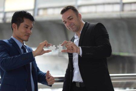 Photo pour Deux hommes d'affaires relient des pièces de casse-tête - image libre de droit