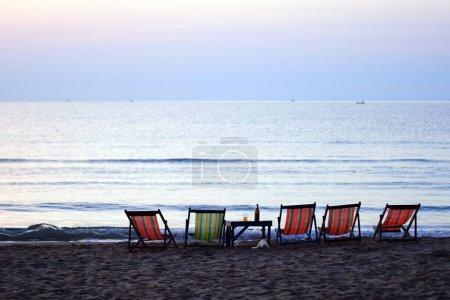 Photo pour Coucher de soleil au bord de la mer avec chaises longues . - image libre de droit