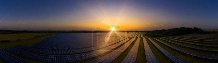Foto de Granja solar moderna panorámica al amanecer en un día de verano - Imagen libre de derechos