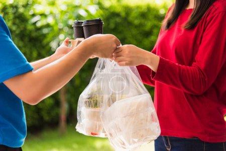 Photo pour Asiatique jeune livreur en uniforme bleu il faisant service d'épicerie donnant riz boîtes alimentaires sacs en plastique à la femme client réception maison avant sous coronavirus pandémique, Retour au nouveau concept normal - image libre de droit
