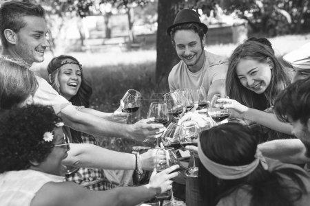 Photo pour Groupe de personnes acclamant et avec des verres rouges de vin - Joyeux amis pique-niquant bbq dans un parc avec de la nourriture et des boissons - Concept du mode de vie des jeunes - Révision en noir et blanc - image libre de droit