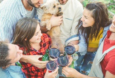 Photo for Happy friends cheering with glasses of red wine outdoor - Young people having fun drinking, toasting and laughing together in a vineyard house - Friendship and youth lifestyle concept - Royalty Free Image