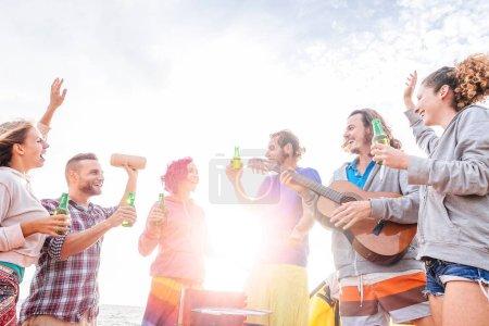 Photo pour Heureux amis boire des bières et jouer de la guitare au barbecue sur la plage - groupe de jeunes s'amuser et de rire ensemble de bbq party - voyages, vacances et jeunes vacances concept lifestyle - image libre de droit