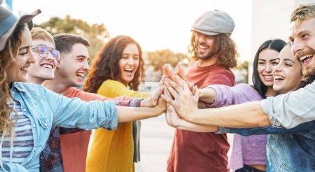 Photo pour Jeunes amis empilant les mains en plein air - Bonne génération de personnes qui s'amusent à se joindre et à célébrer ensemble - Amitié, autonomisation, travail d'équipe, partenariat et concept de style de vie des jeunes - image libre de droit