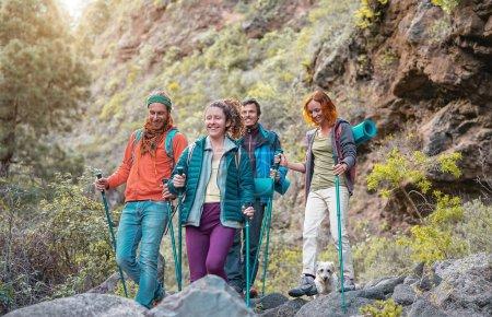 Photo pour Groupe d'amis avec des sacs à dos faisant une excursion de trekking en montagne - Jeunes touristes marchant et explorant la nature sauvage - Trekker, sport, randonnée et concept de voyage - image libre de droit