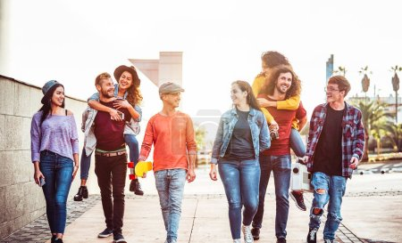 Photo for Group of happy friends having fun outdoor - Young people piggybacking while laughing and walking together in the city center - Friendship, millennial generation, teenager and youth lifestyle concept - Royalty Free Image