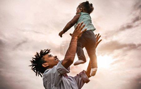 Photo pour Père heureux jouant avec sa petite fille pendant le coucher du soleil - Afro famille s'amuser en plein air - Concept d'enfant, bonheur et parentalité - image libre de droit