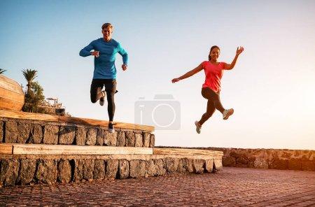 Photo pour S'adapter couple faisant séance d'entraînement course à pied au coucher du soleil en plein air - Les jeunes sportifs jogging à côté de la plage - Style de vie sain et concept de sport - image libre de droit