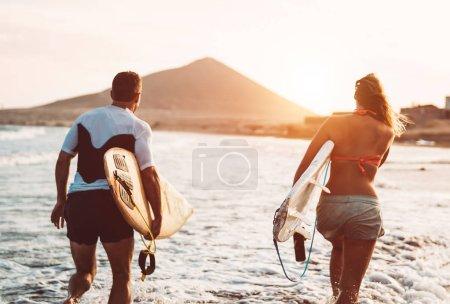 Photo pour Couple surfeur heureux courant avec des planches de surf le long de la côte de la mer - Les gens sportifs s'amusent à surfer ensemble au coucher du soleil - Concept de sport de surf extrême et de style de vie de la relation de jeunesse - image libre de droit