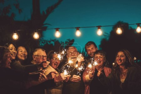 Photo for Happy family celebrating with sparkler at night party outdoor - Group of people with different ages and ethnicity having fun together outside - Friendship, eve and celebration concept - Royalty Free Image