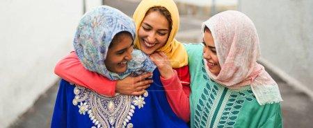 Photo pour Heureuses femmes musulmanes marchant dans le centre-ville - les jeunes filles arabes s'amusent à passer du temps et à rire ensemble en plein air - concept de style de vie gens culture et religion - image libre de droit
