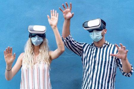 Photo pour Jeune couple portant un masque chirurgical du visage s'amuser avec des lunettes de réalité virtuelle pendant l'épidémie - Les gens millénaires à l'aide novateur vr lunettes casque - génération de jeunes et concept de technologie - image libre de droit