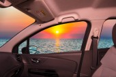 Looking through a car window with view of a scenic sunset on the mediterranean sea
