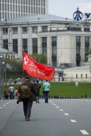 Photo pour Moscou, Russie - 1er mai 2017: Un partisan du Parti communiste russe marche avec un drapeau rouge dans le centre de la capitale - image libre de droit