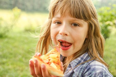 Photo for Child eating a tasty pizza on the nature of the grass in the park - Royalty Free Image