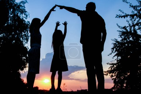 Photo for Happy family together at sunset silhouette - Royalty Free Image