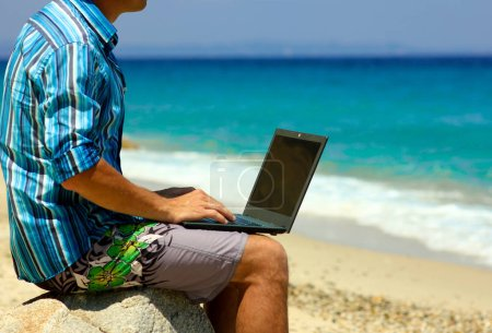 Photo for Man with laptop by the sea in summer - Royalty Free Image