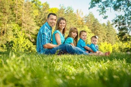 Photo pour Joyeux famille à l'extérieur dans le parc - image libre de droit