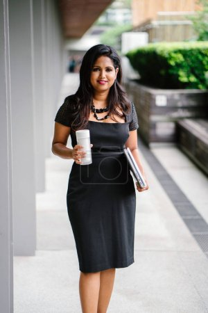 confident Indian Asian woman is walking down a corridor while she holds her laptop, documents and a flask of coffee. She is smiling as she strides down the shaded path in the day.