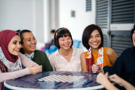 Photo for Asian women laughing and talking sitting together at table - Royalty Free Image