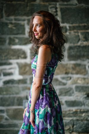 portrait of young woman with curly hair posing standing on grey brick wall background