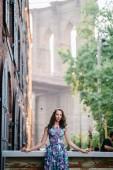 "Постер, картина, фотообои ""young woman with curly hair standing on building background"""