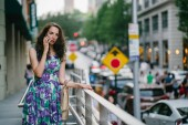 """Постер, картина, фотообои """"outdoor portrait of young woman with curly hair talking on smartphone standing on city background"""""""