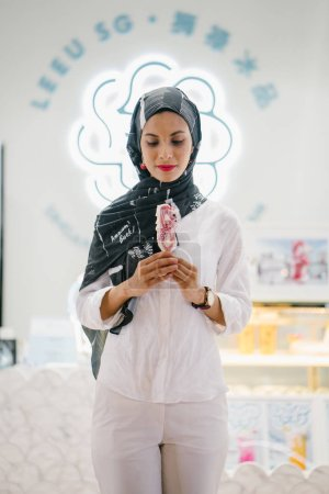 Photo for Portrait of a beautiful muslim woman in hijab with ice cream - Royalty Free Image