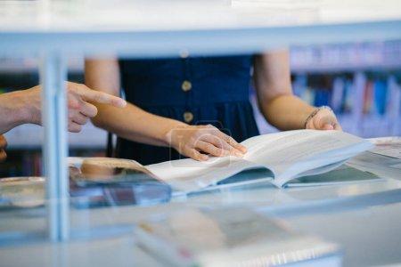Photo pour Jeune femme lecture livre dans la bibliothèque - image libre de droit
