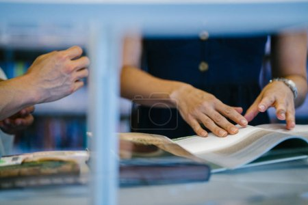 Photo for Young woman reading book in library - Royalty Free Image