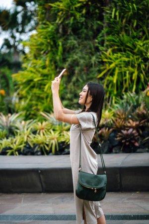 Photo pour Asiatique femme dans un parc avec un téléphone - image libre de droit
