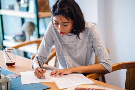 Photo pour Jeune femme assise à la table et écrivant des notes dans son journal - image libre de droit