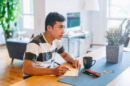 Photo pour Jeune homme écrit dans un cahier à la maison - image libre de droit