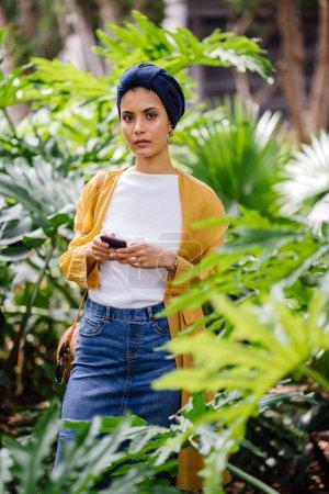 Photo pour Jeune et séduisante Malaise musulmane tenant smartphone dans les mains - image libre de droit
