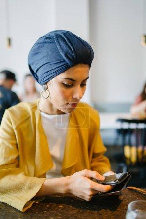 Photo pour Jeune femme utilisant un téléphone portable dans la cuisine - image libre de droit