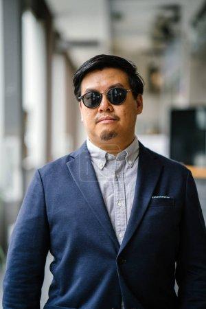 Photo pour Portrait d'un Chinois d'âge moyen asiatique (singapourien) dans un élégant standing décontracté dans la ville. Il est bien habillé et soigné dans un costume de marine, chemise boutonnée oxford avec des lunettes de soleil . - image libre de droit