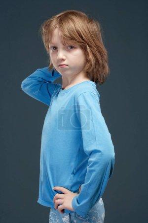 Photo pour Portrait d'un garçon aux longs cheveux blonds en haut bleu . - image libre de droit