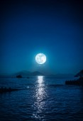 Scenic view of small boat in calm sea water at night time and moon.