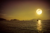 Scenic view of small boat in calm sea water at night time and su