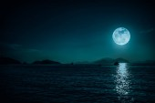Scenic view of small boat in calm sea water at night time and full moon.