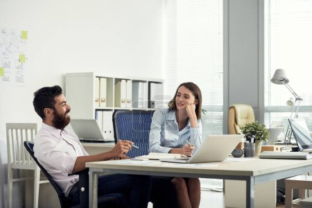 Young bearded man and elegant woman sitting at table in office