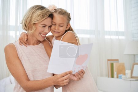 Happy mother reading greeting card from little daughter
