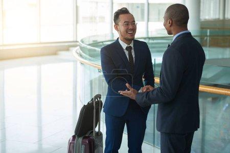 Empresario asiático reuniéndose con compañero afroamericano en terminal aeroportuaria