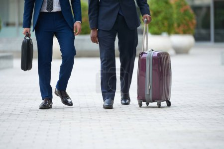 Cropped image of business people with suitcase walking outdoors