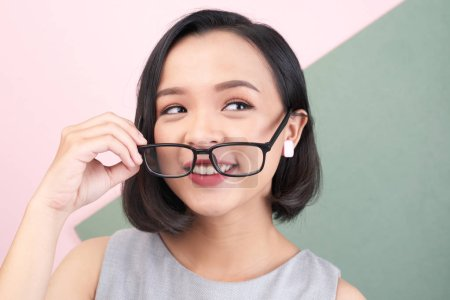 Photo for Attractive smiling Asian young woman putting on glasses - Royalty Free Image