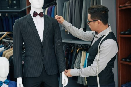 Photo for Tailor measuring suit on mannequin to double check everything - Royalty Free Image