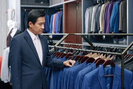 Photo for Middle-aged Vietnamese man searching suit of his size on the rack - Royalty Free Image