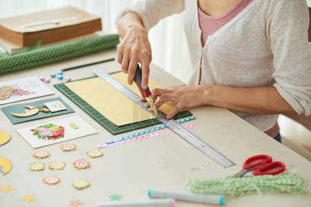 woman sitting at wooden table and making greeting card with cutter knife and ruler on paper