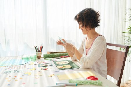 Profile view of cheerful asian woman sitting at wooden table and making greeting card